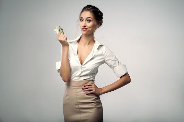 Piękna elegancka młoda biznesowej kobiety pozycja na studiu z szarym tłem