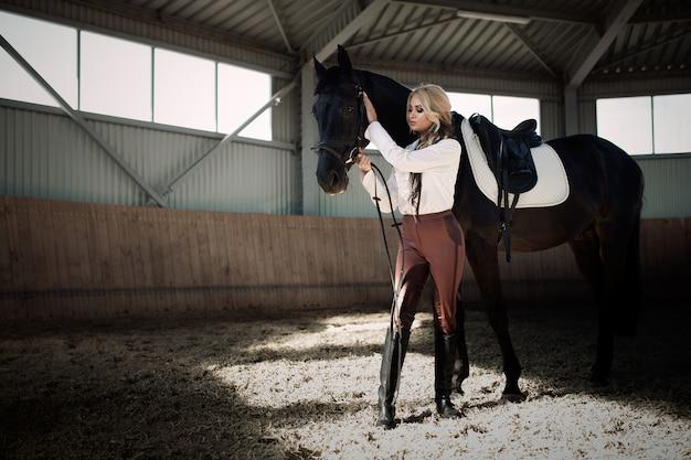 Piękna elegancka młoda blondynki dziewczyna stoi blisko jej końskiego opatrunku munduru rywalizaci