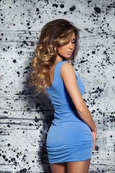 Piękna elegancka młoda kobieta z jasnobrązowymi włosami, makijażem i fryzurą, pozuje w dopasowanej niebieskiej sukni wieczorowej