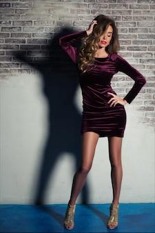 Piękna elegancka młoda kobieta z jasnobrązowymi włosami pozuje w bordowej aksamitnej sukni i złotych obcasach