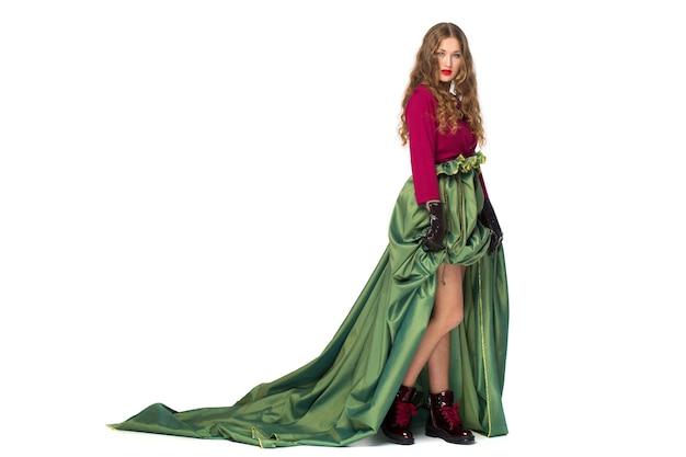 Piękna elegancka nastolatka z długimi kręconymi włosami w dość długiej zielonej spódnicy na białym tle na białej ścianie.