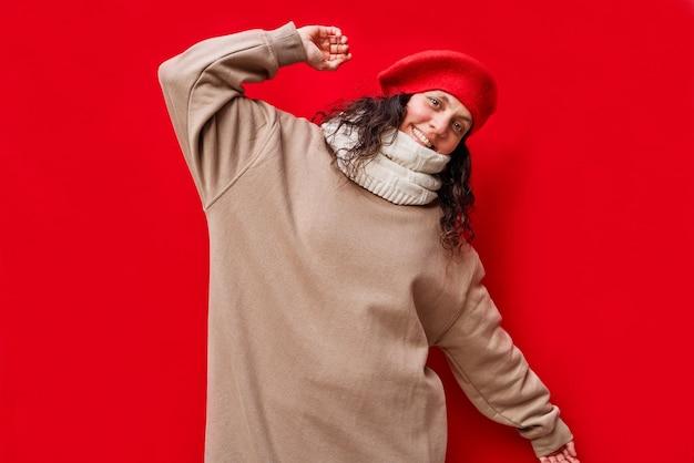 Piękna elegancka, radosna i świąteczna kobieta z czerwoną izolowaną ścianą