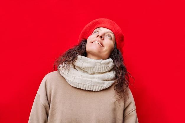 Piękna elegancka wesoła kobieta uśmiecha się i patrzy w górę z odosobnioną czerwoną ścianą