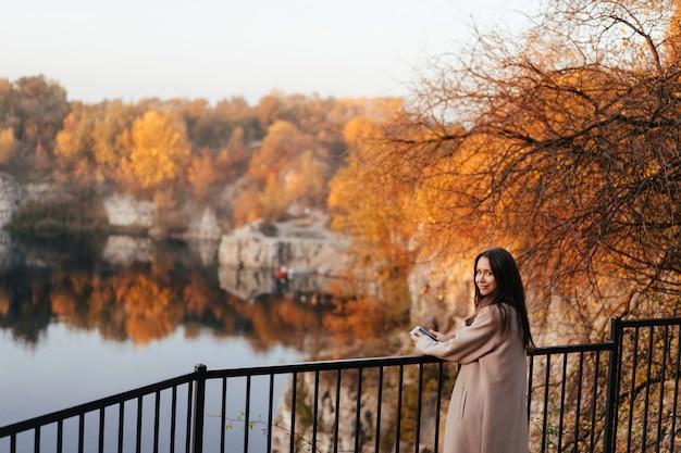 Piękna eleganckiej kobiety pozycja w parku w jesieni