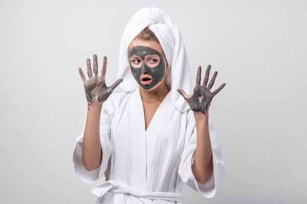 Piękna emocjonalna blondynka pozuje w białym szlafroku z ręcznikiem na głowie, z glinianą maską i glinianymi rękami. patrząc w bok.