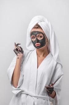 Piękna emocjonalna blondynka pozuje w białym szlafroku z ręcznikiem na głowie, z glinianą maską i glinianymi rękami. pojęcie piękna i zdrowia.