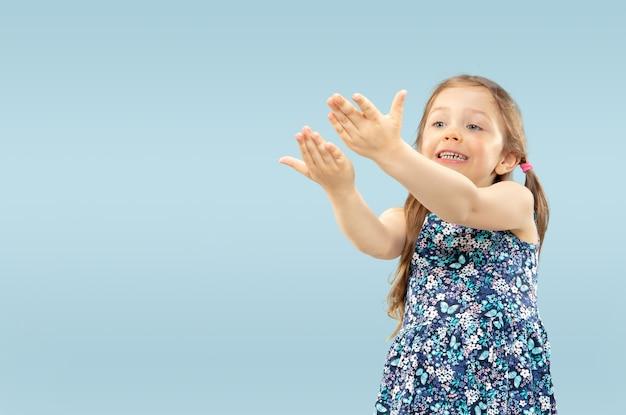 Piękna emocjonalna dziewczynka na białym tle na niebieskiej przestrzeni