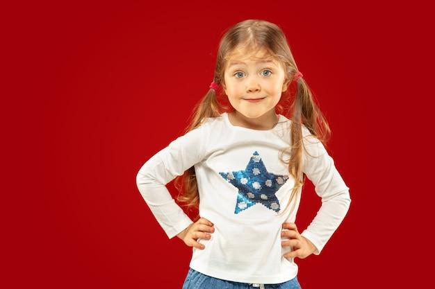 Piękna emocjonalna dziewczynka na białym tle na tle czerwonym studio. półdługi portret szczęśliwego dziecka przedstawiający gest i stojącą. pojęcie wyrazu twarzy, ludzkie emocje, dzieciństwo.