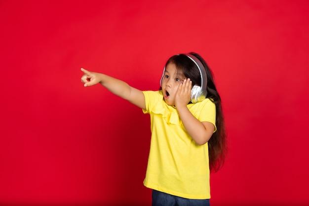 Piękna emocjonalna mała dziewczynka odizolowana na czerwonym półdługości portret szczęśliwego dziecka