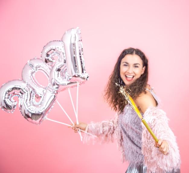 Piękna emocjonalna młoda brunetka z kręconymi włosami świątecznie ubrana, trzymając w ręku świecę z fajerwerkami i srebrne balony na koncepcję nowego roku