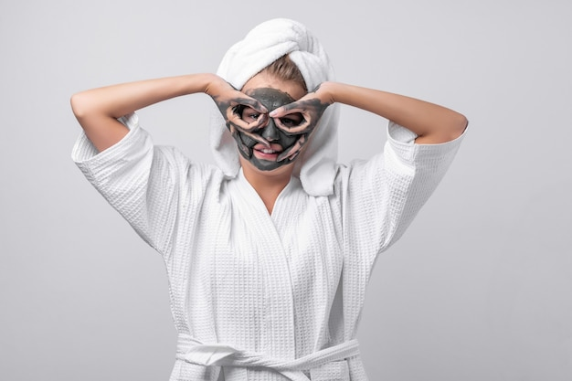 Piękna emocjonalna modelka pozuje w białym szlafroku z ręcznikiem na głowie, zawieszką na szyi, z glinianą maską i glinianymi dłońmi. błazenowanie w kamerę. robienie maski z palców.