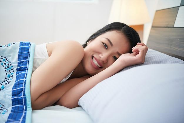 Piękna etniczna kobieta cuddling w łóżku