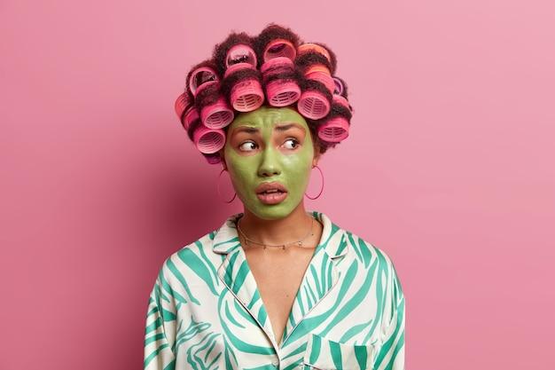 Piękna etniczna kobieta ma zmartwiony wyraz twarzy, odwraca wzrok, nakłada zieloną maskę, aby zmniejszyć drobne zmarszczki, nosi szlafrok odizolowany od różu. kosmetologia, wellness, stylizacja włosów