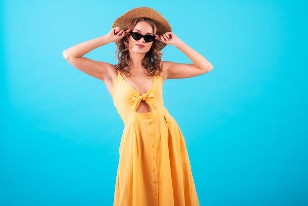 Piękna europejka dziewczyna z uroczym uśmiechem, w modnej jasnożółtej sukience, okularach przeciwsłonecznych i słomkowym kapeluszu