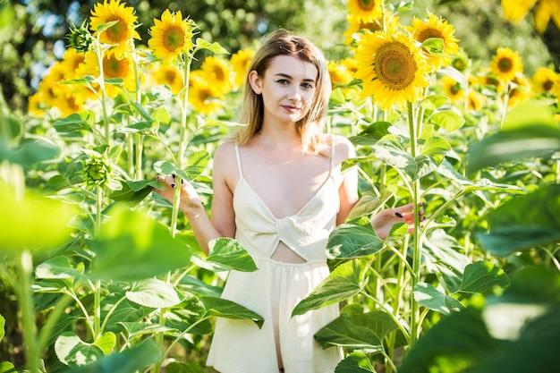 Piękna europejska dziewczyna w białej sukni na charakter z słonecznikami