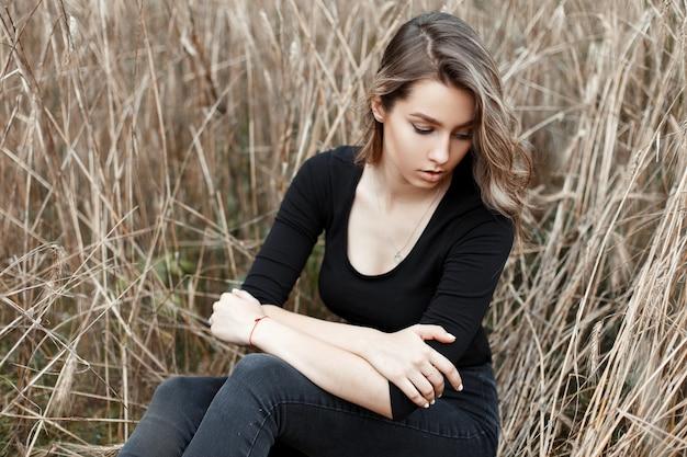Piękna europejska młoda kobieta w dżinsach vintage w czarnej modnej koszulce siedzi wśród jesiennej suchej trawy na polu