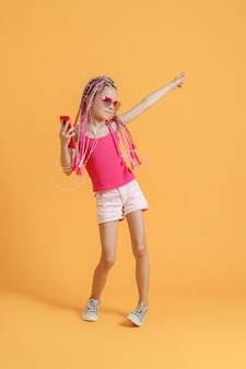 Piękna europejska nastolatka z dredami z telefonem komórkowym w dłoni