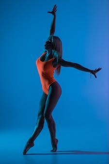 Piękna fajna młoda sprawna kobieta gimnastyczka w niebieskiej sukience sportowej, ćwicząca, wykonująca element gimnastyki artystycznej, skacząca, robi skok w powietrzu, tańcząca