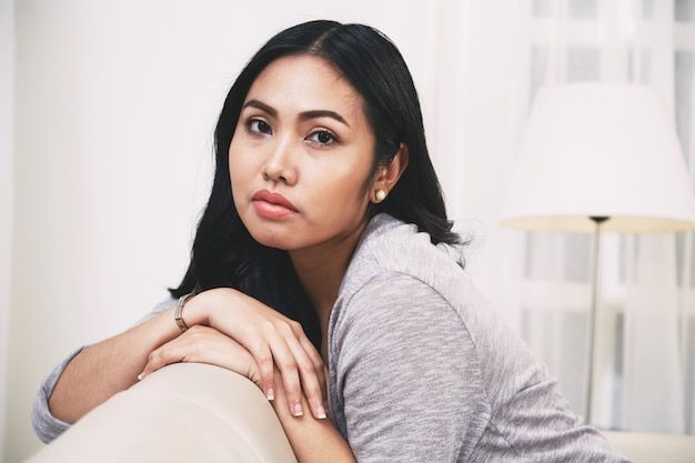 Piękna filipińska kobieta relaksuje na miękkiej leżance