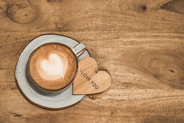 Piękna filiżanka kawy w kształcie serca z drewnianym sercem z napisem kocham cię na drewnianym tle. koncepcja walentynki. selektywna ostrość.