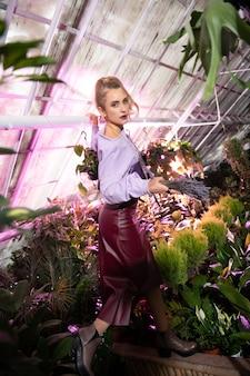 Piękna flora. atrakcyjna poważna kobieta trzymająca bukiet kwiatów stojąc w szklarni
