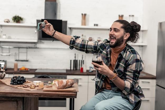 Piękna fotka. zachwycony szczęśliwy mężczyzna trzymający kieliszek wina podczas robienia selfie