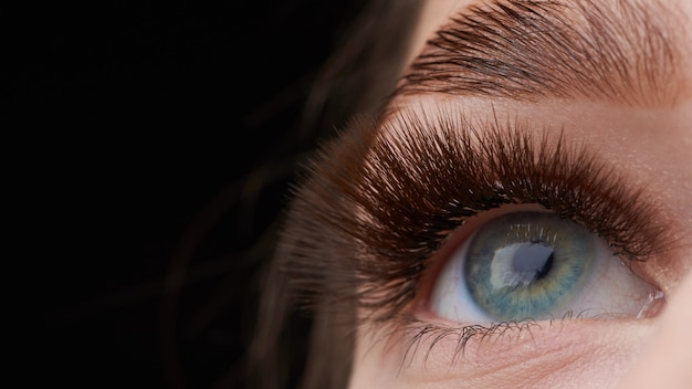 Piękna fotografia makro kobiecego oka z ekstremalnym makijażem długich rzęs