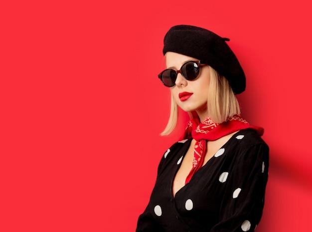Piękna francuska kobieta w berecie na czerwieni ścianie