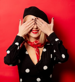 Piękna francuska kobieta w berecie na czerwonej ścianie