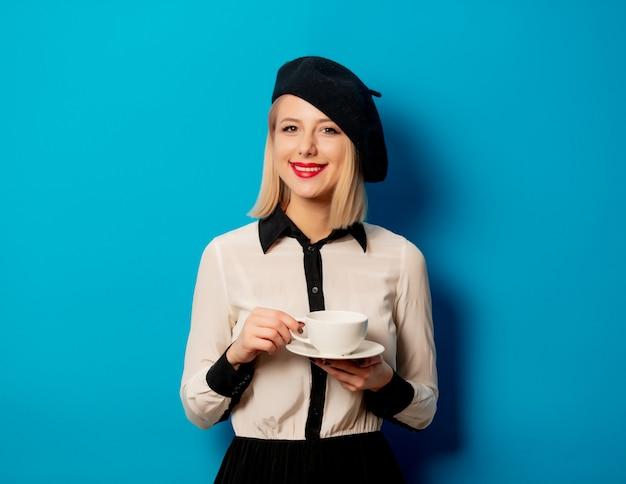 Piękna francuska kobieta w berecie trzyma białą filiżankę kawy