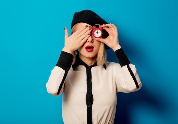 Piękna francuska kobieta w berecie trzyma czerwonego budzika na błękit ścianie