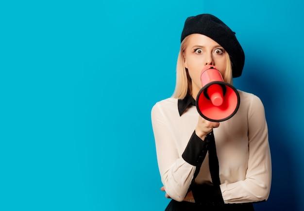 Piękna francuska kobieta w berecie trzyma głośnika na błękit ścianie