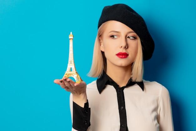Piękna francuska kobieta w berecie trzyma miniaturową wieżę eifla