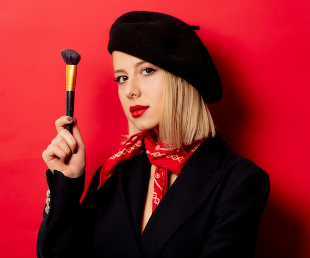 Piękna francuska kobieta w berecie z pędzlem do makijażu na czerwonej ścianie