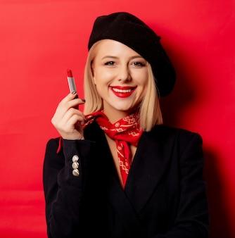 Piękna francuska kobieta w berecie z szminką na czerwonej ścianie