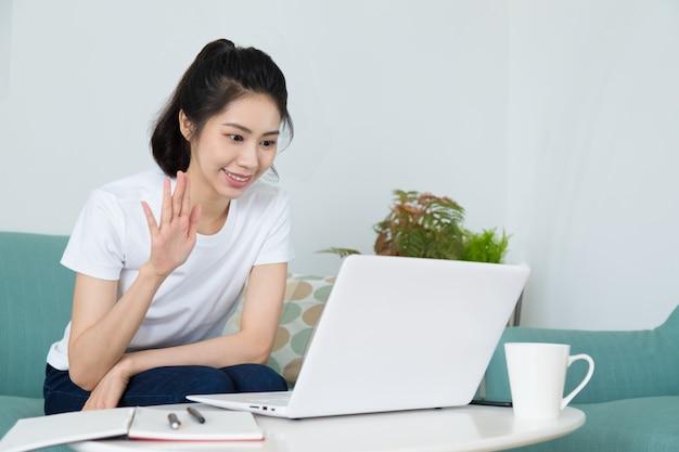 Piękna freelancerka rozmawia na wideokonferencji online z laptopem w domu. ucz się na odległym kursie online. porozmawiaj podczas rozmowy wideo ze znajomym lub krewnym.