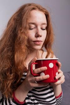 Piękna frekles kobieta cieszy się filiżankę kawy