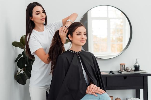 Piękna fryzjer robi fryzurę swojemu klientowi