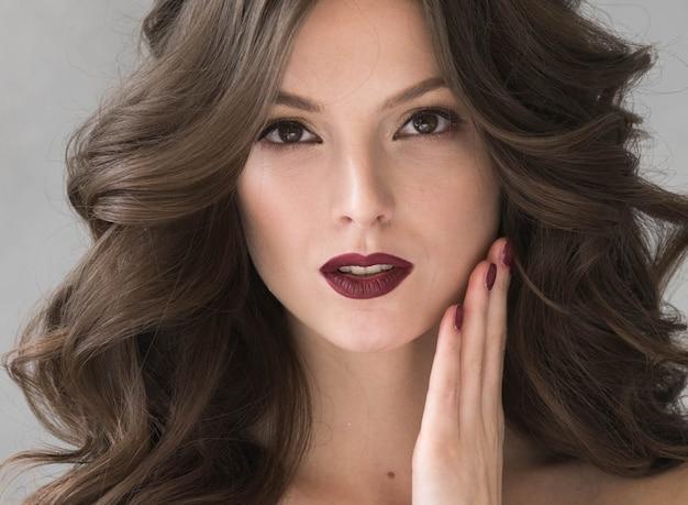Piękna fryzura kobieta uroda włosy moda makijaż czerwona szminka. strzał studio.