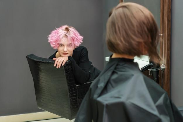 Piękna fryzura młodej kobiety po farbowaniu włosów, inna kobieta robi sobie włosy