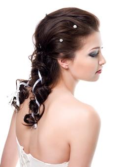 Piękna fryzura ślubna dla młodej ładnej panny młodej brunetki