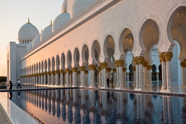 Piękna galeria słynnego meczetu sheikh zayed white w abu dhabi, zjednoczone emiraty arabskie. odbicia o zachodzie słońca