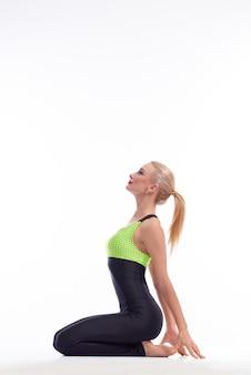 Piękna gimnastyczka siedząca z wdziękiem na białym tle