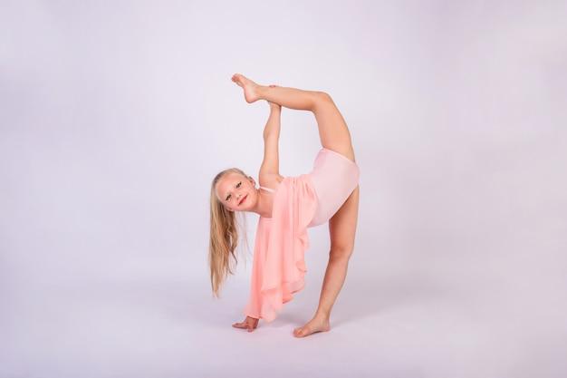 Piękna gimnastyczka w brzoskwiniowym stroju kąpielowym stoi w gimnastycznej pozie i patrzy w kamerę na białej ścianie na białym tle