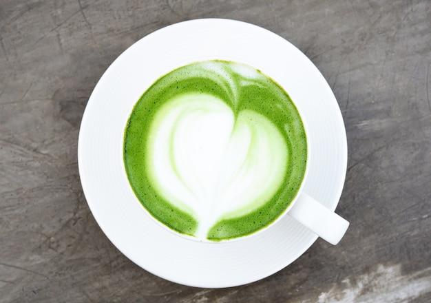 Piękna gorąca zielona herbata w białej filiżance na cemencie zgłasza tło