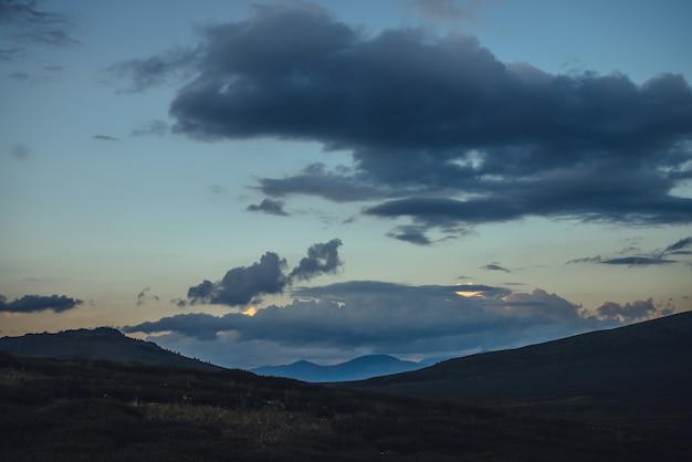 Piękna górska sceneria ze złotym światłem świtu w zachmurzonym niebie. malowniczy krajobraz górski z rozświetlonym kolorem na niebie o zachodzie słońca. sylwetki gór na wschód. złote oświetlające światło słoneczne na niebie