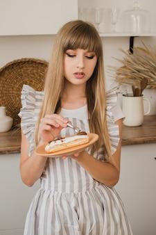 Piękna gospodyni domowa lub cukiernik trzyma w dłoni talerz z eklerem i ozdabia go