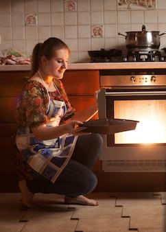 Piękna gospodyni domowa siedzi obok piekarnika i trzyma patelnię w pobliżu gorącego piekarnika