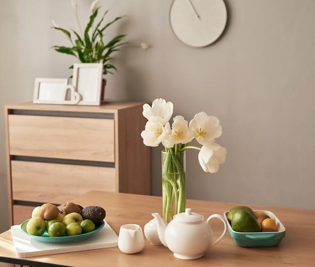 Piękna herbata na drewnianym stole. wystrój wnętrz domu, bukiet kwiatów w wazonie, stół z zestawem czajnika.