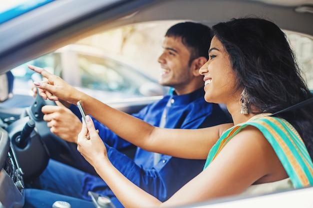 Piękna hinduska w samochodzie wskazująca drogę do kierowcy
